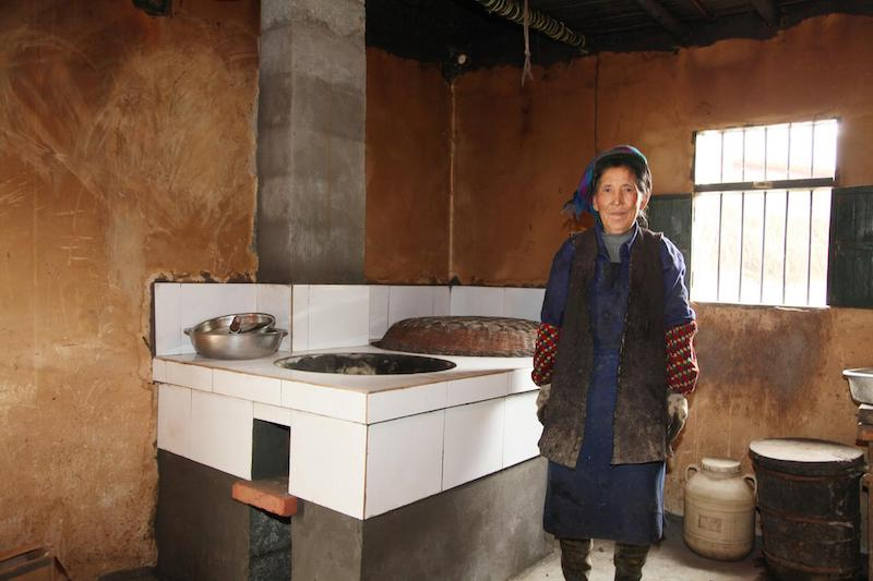 Image: A woman stands in the kitchen with her new stove – the built-in stoves are designed to cook traditional food and to be long-lasting.